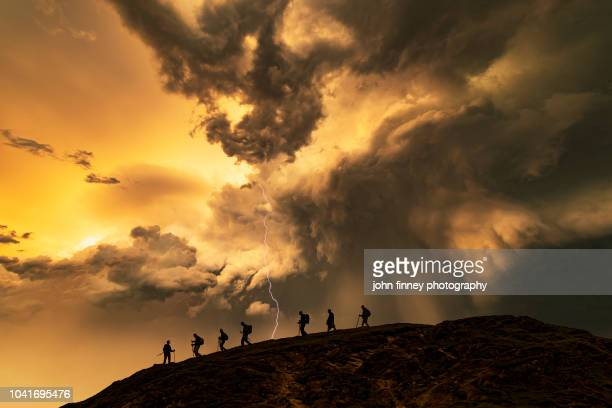 hikers on the storm at sunset, catbells mountain, lake district. uk. - whitehaven cumbria stock pictures, royalty-free photos & images