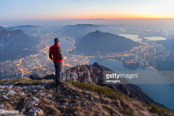 hikers on the top of the mountain above the city - turista foto e immagini stock