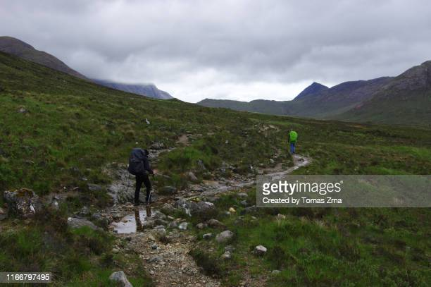 hikers on their way in landscape in the wild valley of glen sligachan with surrounding peaks of the red hills - glen sligachan photos et images de collection