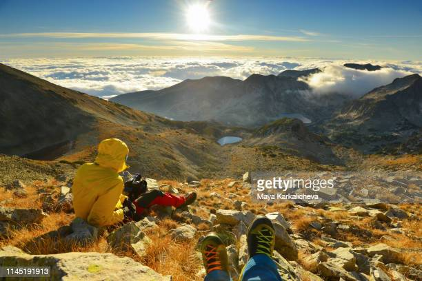 hikers on top of a mountain watching the sunrise - pirin national park stock pictures, royalty-free photos & images