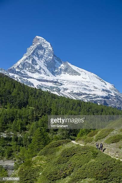 Hikers on walking trail below the Matterhorn mountain in the Swiss Alps near Zermatt Switzerland