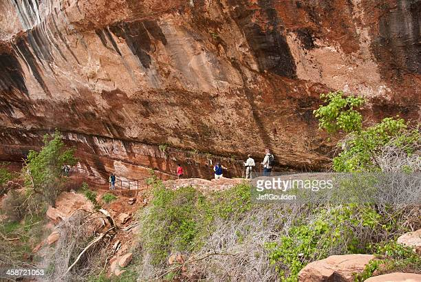 People Pass Beneath Cliff on The Way to Emerald Pools