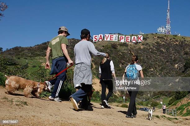 Hikers pass near the iconic 450footlong Hollywood sign after activists covered it with banners during an effort to prevent the building of houses...