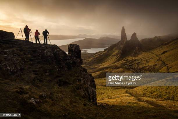 hikers photographing while standing on cliff against sky - famous place stock pictures, royalty-free photos & images
