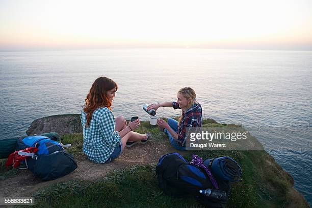 hikers pour hot drink on cliff top - picnic stock pictures, royalty-free photos & images