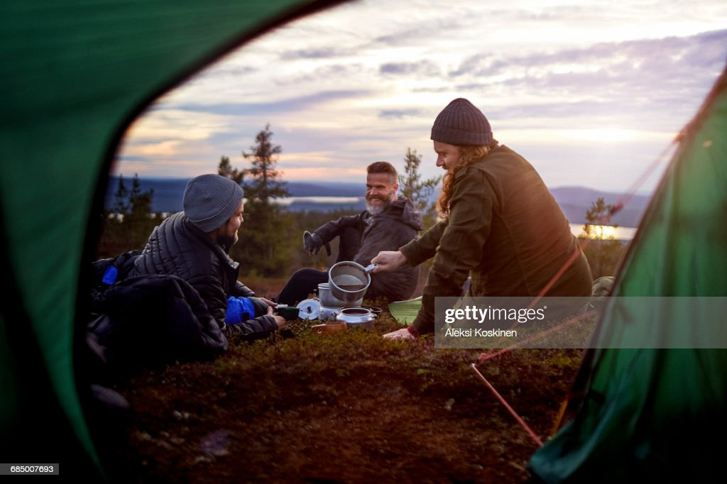 Hikers preparing meal, chatting in front of tent, Keimiotunturi, Lapland, Finland : Stock-Foto