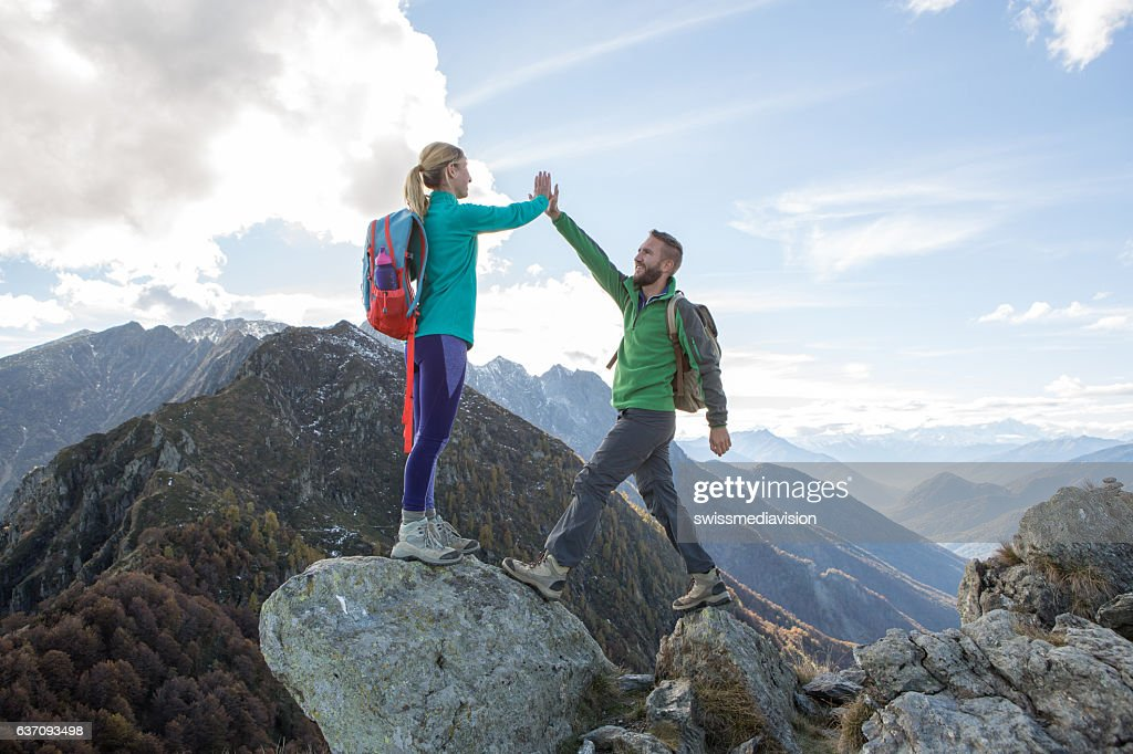 Hikers reaching mountain top celebrating with high five : Stock-Foto