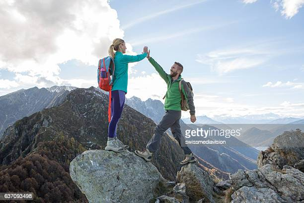 Hikers reaching mountain top celebrating with high five