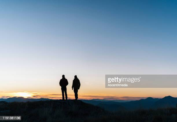 hikers relaxes above mountain valley at sunrise - look back at early colour photography stock pictures, royalty-free photos & images