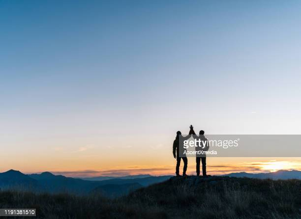 hikers relaxes above mountain valley at sunrise - summit stock pictures, royalty-free photos & images