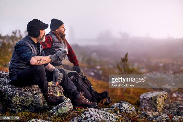 Hikers relaxing with coffee on rocky field, Sarkitunturi, Lapland, Finland