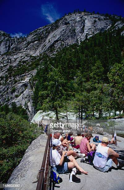 Hikers rest for sandwiches on top of Vernal Falls in Yosemite.