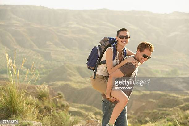Hikers Riding Piggyback on Country Road