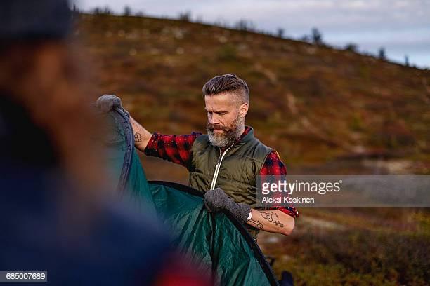 Hikers setting up tent, Keimiotunturi, Lapland, Finland
