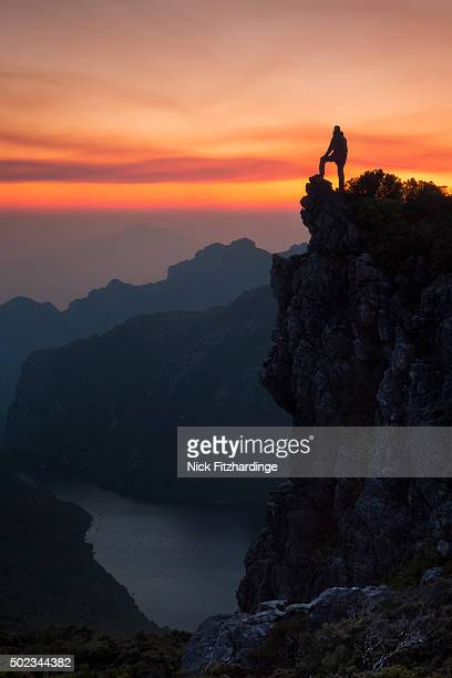 A hiker's silhouette standing on the cliffs edge in the Western Arthur mountain range at sunset, South West National Park, Tasmania, Australia