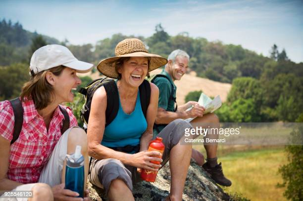 hikers siting on rock and laughing - baby boomer stock pictures, royalty-free photos & images