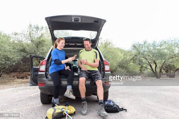 hikers sitting in car texting on cell phones - 送る ストックフォトと画像