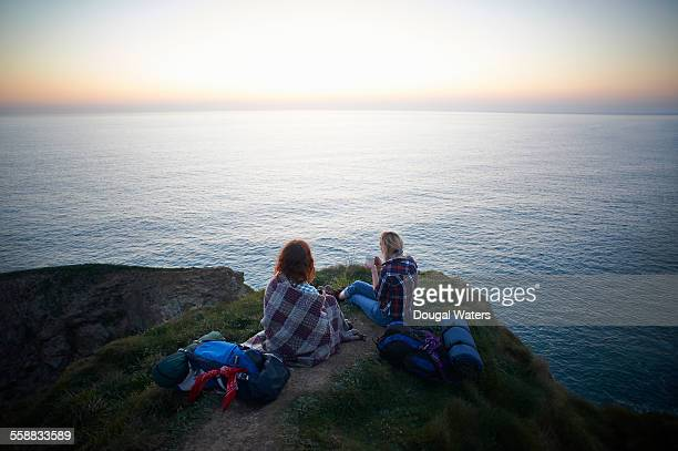 Hikers sitting on cliff top looking out to sea