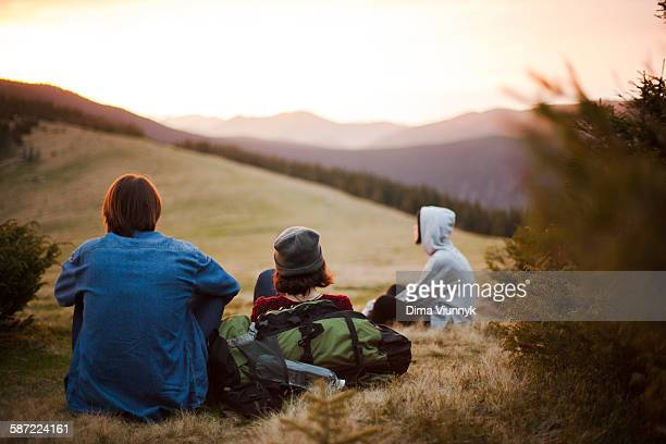 Hikers sitting on grass hill