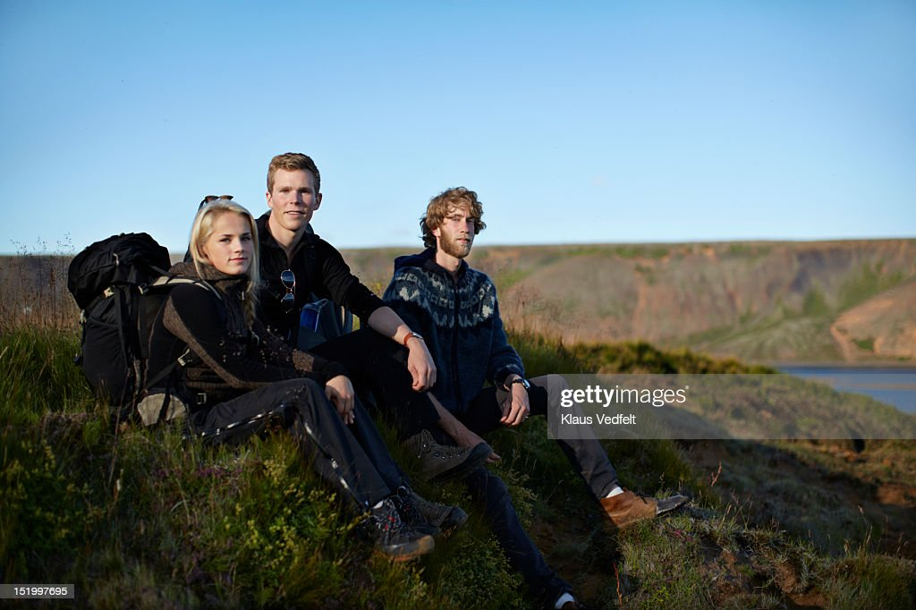 3 hikers sitting on grasshill looking in camera : Foto de stock