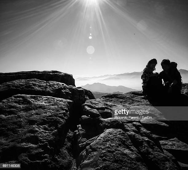Hikers Sitting On Rock Against Bright Sky