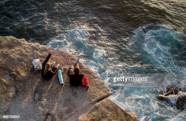 Hikers sitting on the edge of a cliff taking a break from the walk