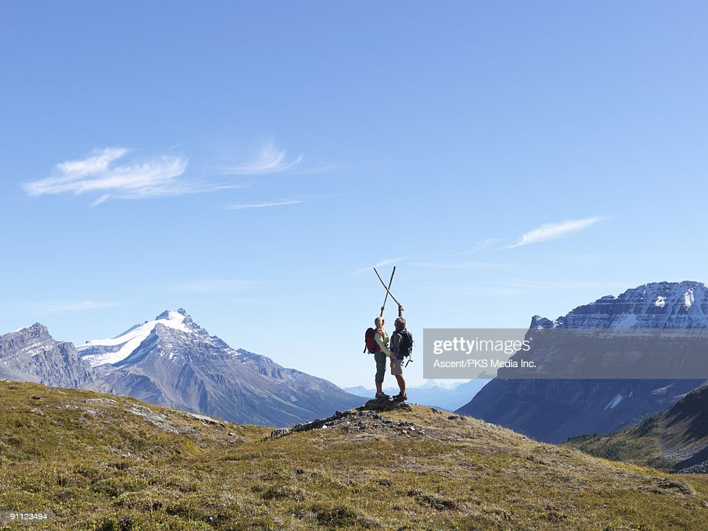 Hikers stand on knoll in mtn meadow, hiking poles : Stock Photo