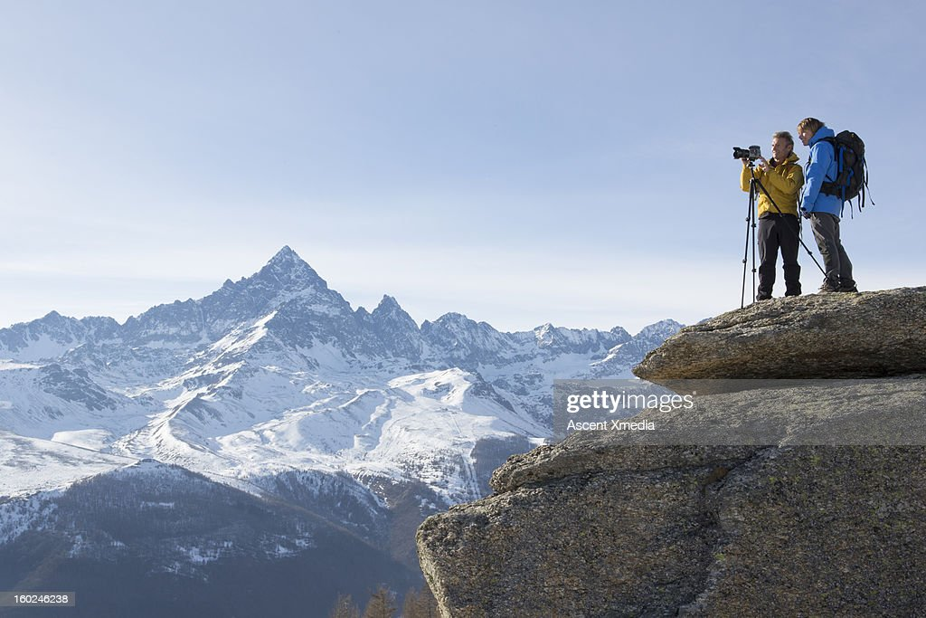 Hikers stand on mountain summit, taking picture : ストックフォト