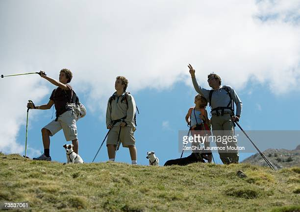 Hikers standing, looking at and pointing to view