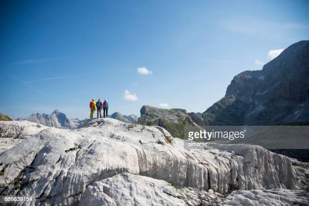Excursionistas de pie sobre una montaña de la roca