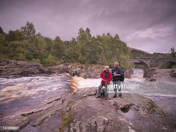 Hikers standing on rocks by flowing Scottish river