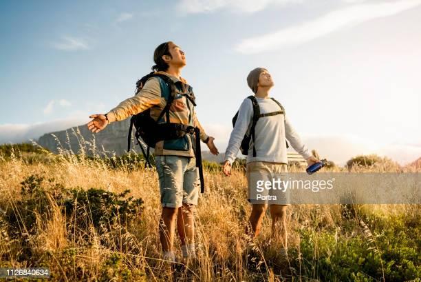 丘の上に腕を広げて立っているハイカー - 若い男性だけ ストックフォトと画像