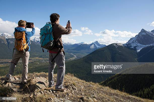 Hikers take pictures with tablet/smartphone,summit