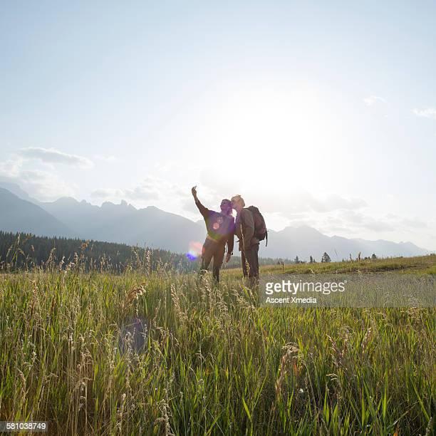 Hikers take selfie in mountain meadow, sunrise