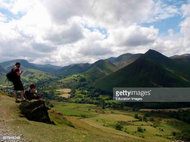 Hikers taking a break on Cat Bells Fell, The Lake District, Cumbria, UK.
