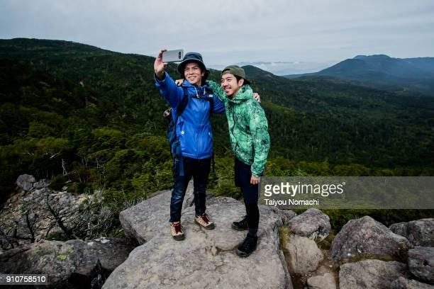 hikers taking pictures - アウトドア ストックフォトと画像