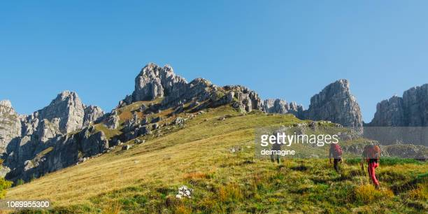 hikers team on mountain trail - lombardy stock pictures, royalty-free photos & images