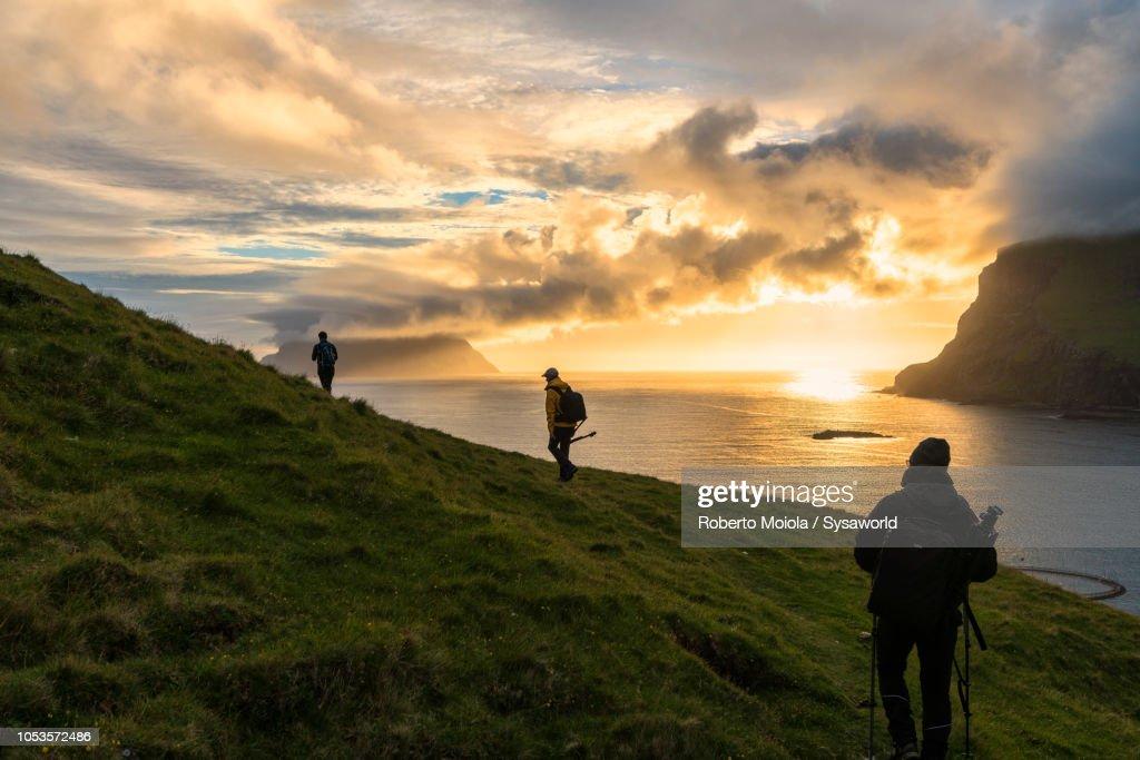Hikers towards Drangarnir rock, Vagar island : Stock Photo
