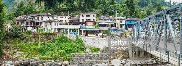 hikers trekking annapurna circuit past teahouse lodges himalayas panorama nepal - annapurna circuit stock photos and pictures