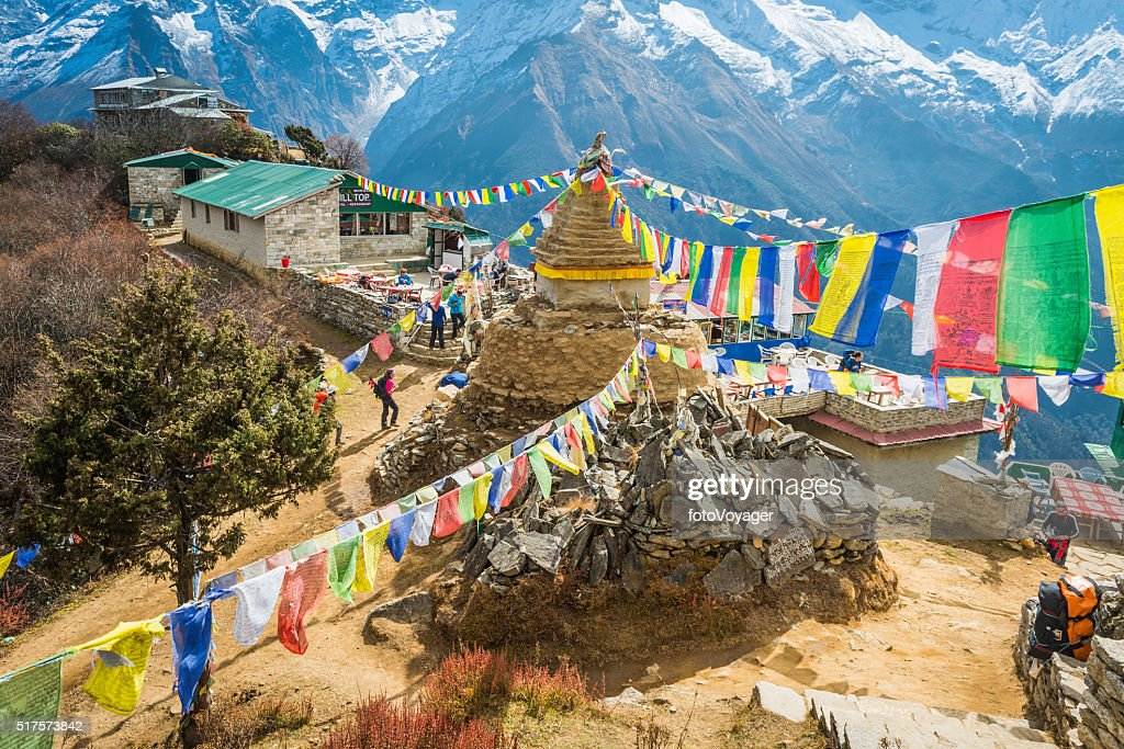 Hikers trekking colourful Buddhist prayer flags Everest trail Himalayas Nepal : Stock Photo