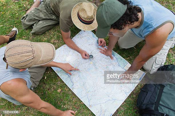 Hikers using compass and looking at map together, high angle view