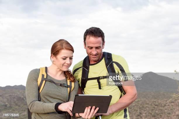 Hikers using digital tablet in desert