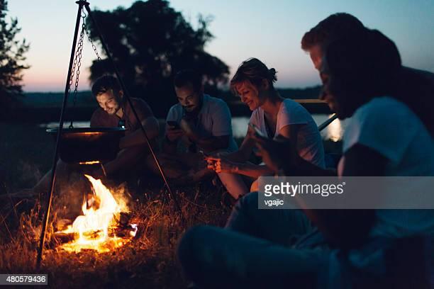 Hikers Using Smart Phones Around Campfire.