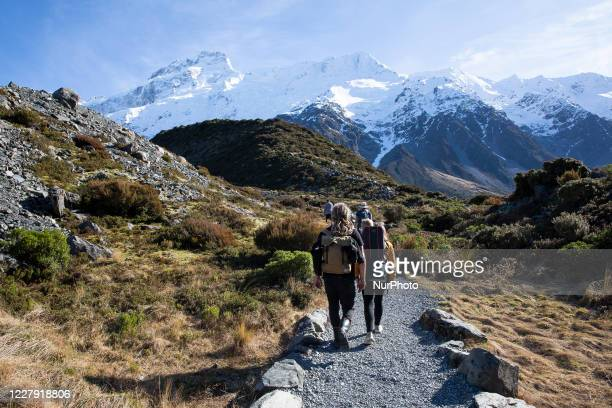 Hikers walk in the Hooker Valley track at Aoraki / Mount Cook National Park in the South Island, New Zealand, on August 05, 2020.The lookout point...