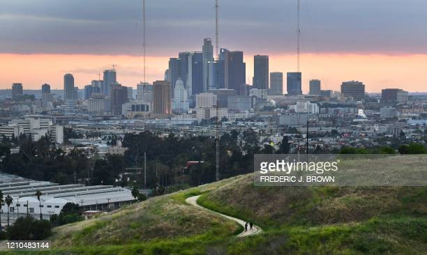 Hikers walk on a trail with a view of the Los Angeles city skyline in Los Angeles on April 20, 2020. - A new study testing adults for COVID-19...