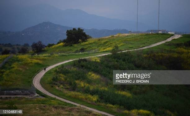 Hikers walk on a trail with a view of the San Gabriel Mountains in Los Angeles on April 20, 2020. - A new study testing adults for COVID-19...