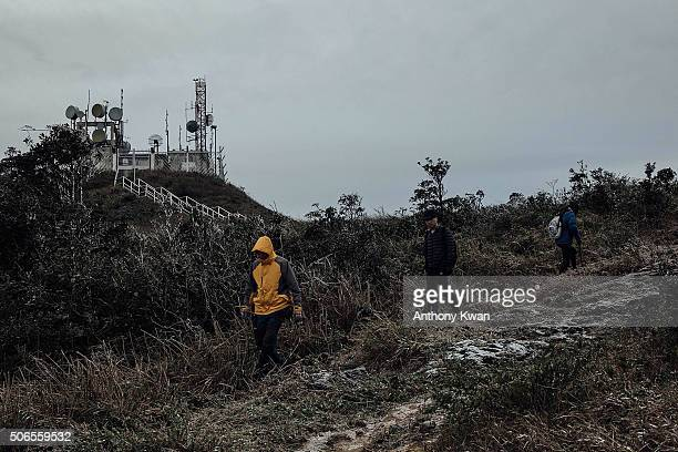 Hikers walk on icy grass in subzero temperature at Kowloon Peak on January 24 2016 in Hong Kong Hong Kong Hong Kong was hit by a cold snap today with...