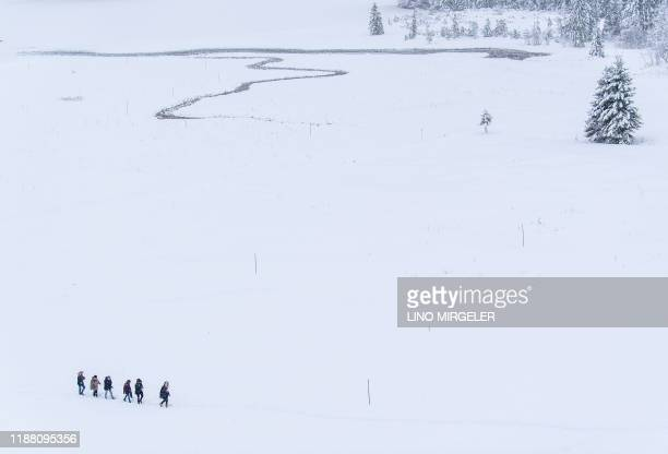 Hikers walk through the snowy landscape in Spitzingsee, southern Germany, on December 12, 2019. / Germany OUT