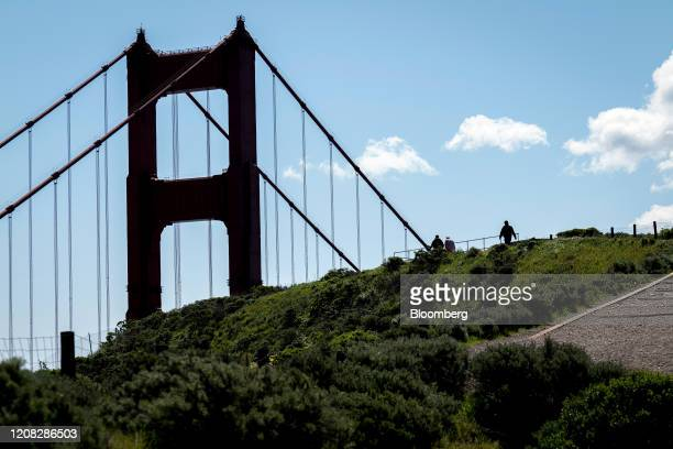 Hikers walk up a trail to a Golden Gate Bridge viewing location in Sausalito, California, U.S., on Thursday, March 26, 2020. Governor Newsom on March...