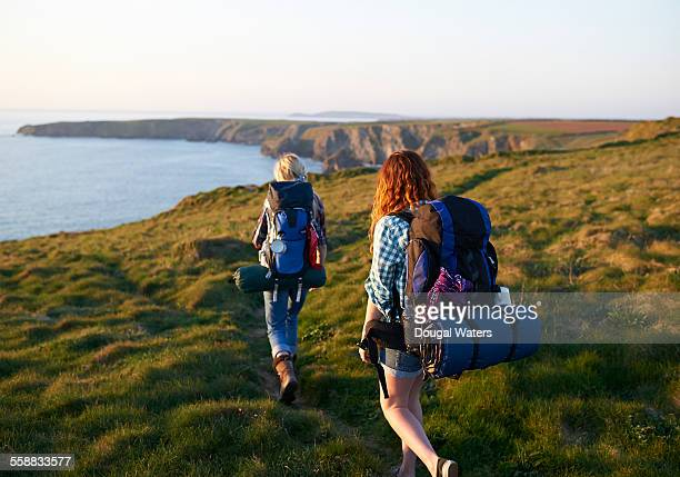hikers walking along coastal path - exploration stock pictures, royalty-free photos & images